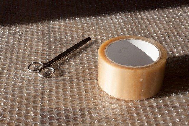 Umzugsmaterialien in Form von Luftpolsterfolie, Schere und Paketband.
